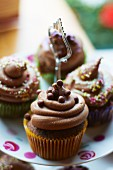 Chocolate cupcakes with sugar pearls on a cake stand
