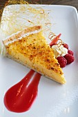A slice of lemon tart with raspberry sauce