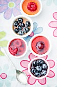 Several mini fruit jellies in eggcups