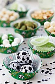 Various snacks arranged in muffin cases with football decorations