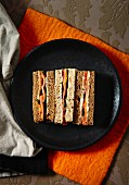 Finger sandwiches on a black plate