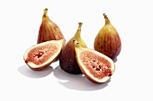 Fresh figs, whole and halved, against a white background