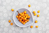 Sea buckthorn berries in a small bowl and on a tablecloth (view from above)