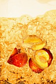 Peach iced tea with chunks of peach (close-up)