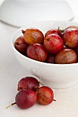 Red gooseberries in a white bowl and in front