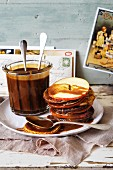 A stack of pancakes and apple slices, with caramel sauce