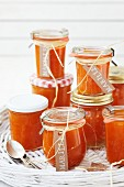 Several jars of apricot jam on a wicker tray