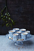 Parfaits in front of a wooden wall with a sprig of mistletoe