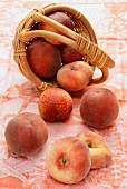 Peaches and nectarines in and in front of a basket