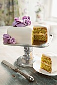 A wedding cake with purple flowers, with one slice cut