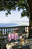Gedeckter Tisch mit Nizzasalat auf einer Terrasse mit Ausblick auf die Stadt Nizza