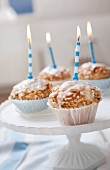Four muffins with birthday candles