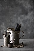 Old tin jugs and a tin cup with cutlery