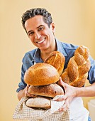 A man in an apron holding assorted freshly baked loaves of bread