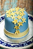 A layer cake iced with blue fondant, decorated with marzipan flowers and sugar balls
