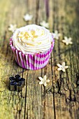 A cupcake with buttercream icing and marzipan flowers
