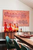 Aborigine Malerei über 50er Jahre Sideboard mit Sammlung kunstvoller Glasflaschen (Blenko) und Stuhlklassiker Executive (Saarinen) an Esstisch im Vordergrund