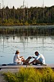 Mann, Frau und Hund in der Abendsonne auf einem Holzsteg am See