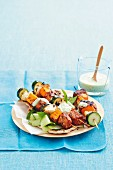 Tandoori chicken skewers with vegetables, served with a yoghurt dip and pita bread