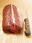 Raw saddle of venison with a sharp knife
