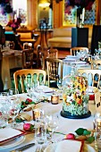 A celebration table with a floral arrangement under a glass cloche