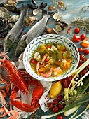 A bowl of fish soup, surrounded by ingredients