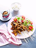 Satay skewers with a cucumber and tomato salad and satay sauce