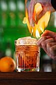 Flambierter Cocktail mit Orange