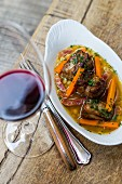 Pork short ribs with bacon carrots, and glass of red wine
