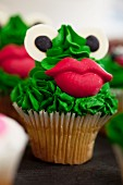A party cupcake decorated with a frog's face