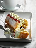 Doughnut filled with jam and cream, split open