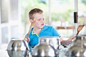 A boy using saucepans as a drum kit