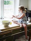 Kleines Mädchen sitzt auf Küchenschrank neben Backzutaten beim Fenster