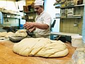 Bäcker wiegt Brotteig in der Backstube