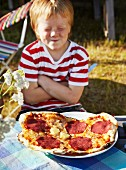 Boy sitting with pizza, eyes closed