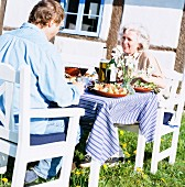 A couple eating lunch in the garden, Skane, Sweden.