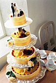 An elegant four-tier wedding cake with a miniature bride and groom