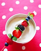 A berry skewer with mint on a bowl of whipped cream
