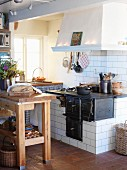 Rustic country-house kitchen with chopping block table in front of built-in, tiled oven with extractor hood