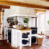 Schneideblocktisch neben rustikalem Küchenherd in skandinavischem Landhaus