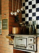 Vintage kitchen cooker built into brick wall against chequered wall tiles