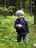 Little girl holding pot in summer forest