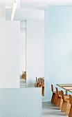 Designer Stühle und Tische aus Holz, abgetrennt mit raumhohen Trennelementen in einem Restaurant