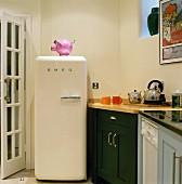 Frei stehender Kühlschrank im Retrostil neben verschiedenen Unterschränken in einer Küche