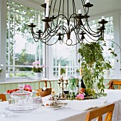 Wrought iron chandelier above white, set table in window bay