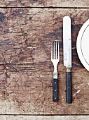 Gabel, Messer und Teller auf Holztisch (Draufsicht)