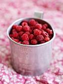 Metal mug full of raspberries