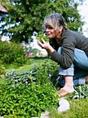 Woman smelling herbs in garden