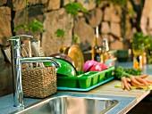 Spülbecken mit Geschirrablage vor Natursteinwand