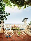 Kleiner Tisch mit zwei Stühlen vor Balustrade auf Terracotta-Terrasse mit Meerblick